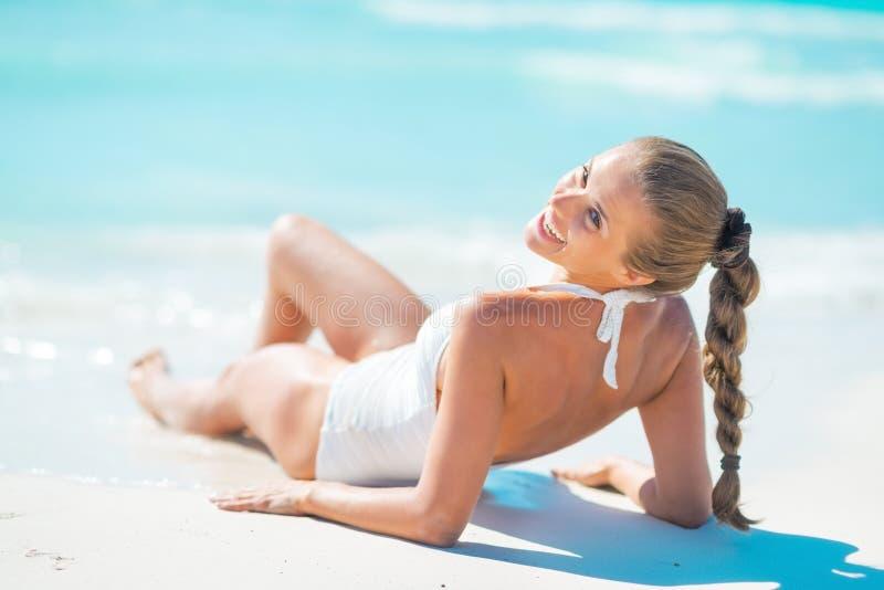 Jeune femme heureuse s'étendant sur la plage image stock