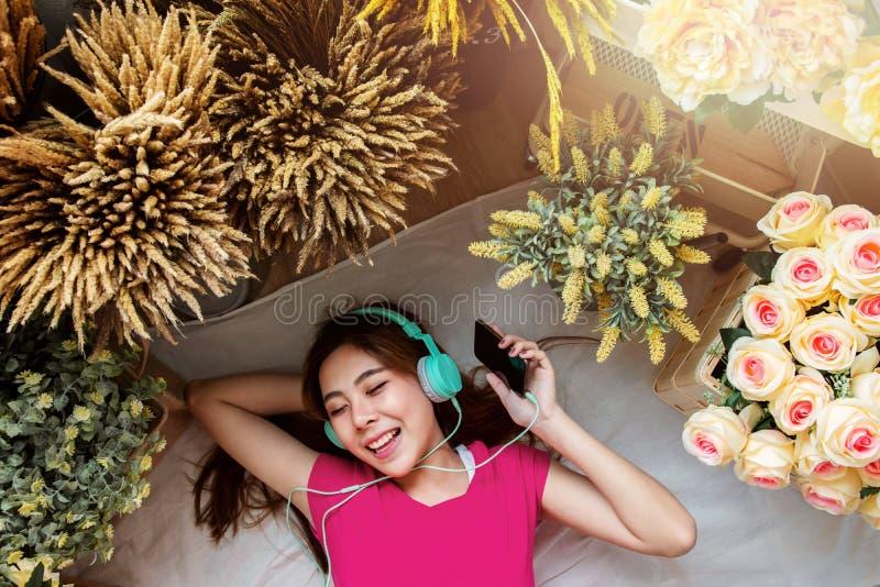 Jeune femme heureuse s'étendant sur le plancher en musique de écoute photos libres de droits