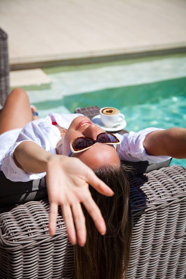 Jeune femme heureuse s'étendant sur le poolside de chaise longue images stock