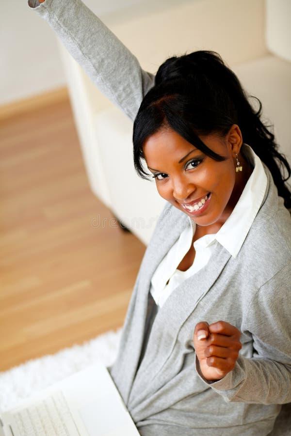 Jeune femme heureuse s'asseyant à la maison sur l'étage photos stock