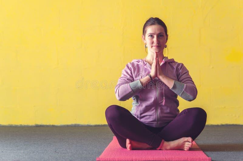 Jeune femme heureuse s'asseyant après session de yoga image stock