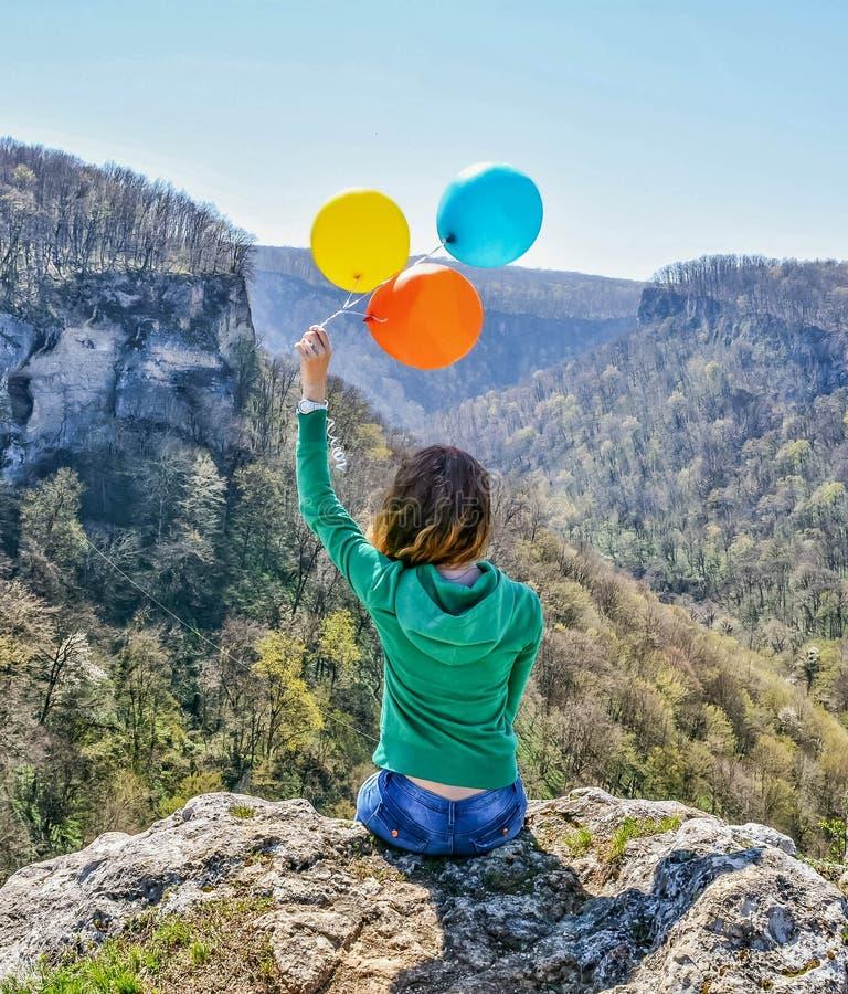 Jeune femme heureuse s'asseyant au bord de la falaise tenant les ballons colorés dans des ses mains photo stock