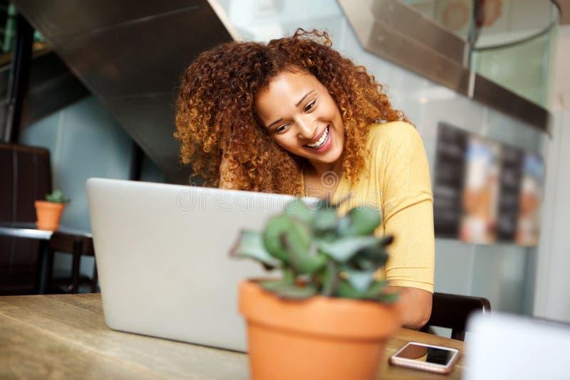 Jeune femme heureuse s'asseyant au café regardant l'ordinateur portable image stock