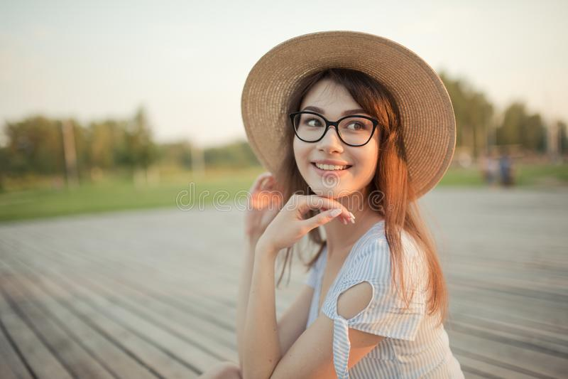 Jeune femme heureuse s'asseyant en parc Fond vert arri?re images stock