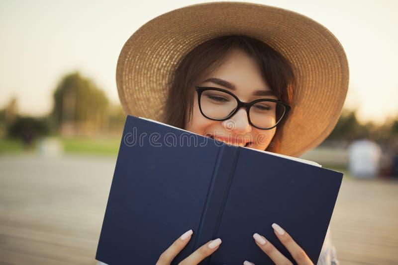 Jeune femme heureuse s'asseyant en parc Souriant et tenant un livre dans des ses mains photo libre de droits
