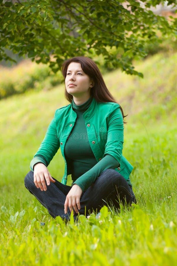Jeune femme heureuse s'asseyant sur l'herbe images libres de droits