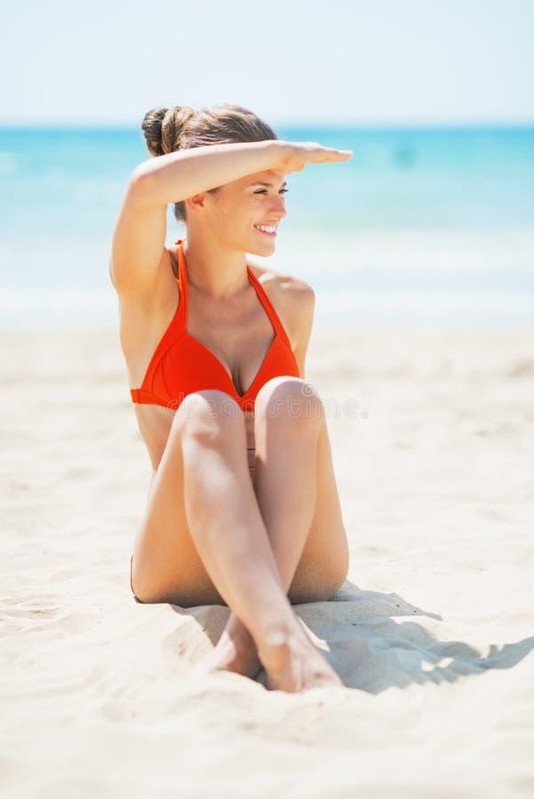 Jeune femme heureuse s'asseyant sur la plage et regardant sur l'espace de copie image libre de droits