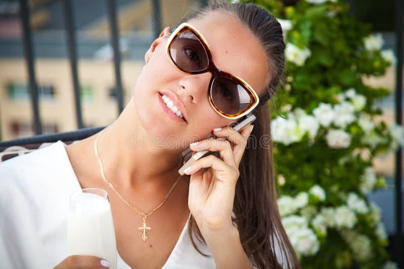 Jeune femme heureuse s'asseyant sur le terasse et parlant au téléphone photos stock