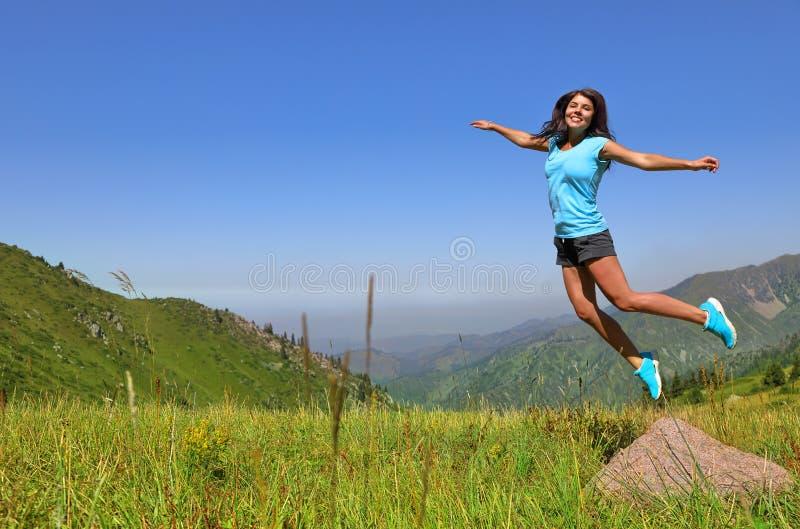 Jeune femme heureuse sautant contre des montagnes photographie stock