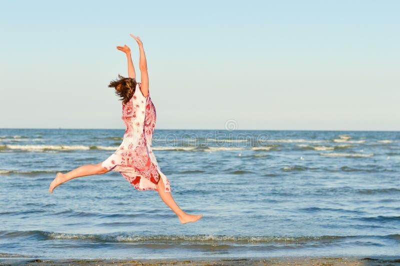 Jeune femme heureuse sautant haut au bord de la mer photographie stock