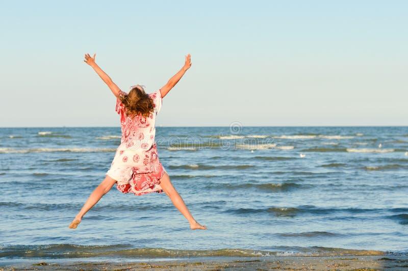 Jeune femme heureuse sautant haut au bord de la mer photos libres de droits