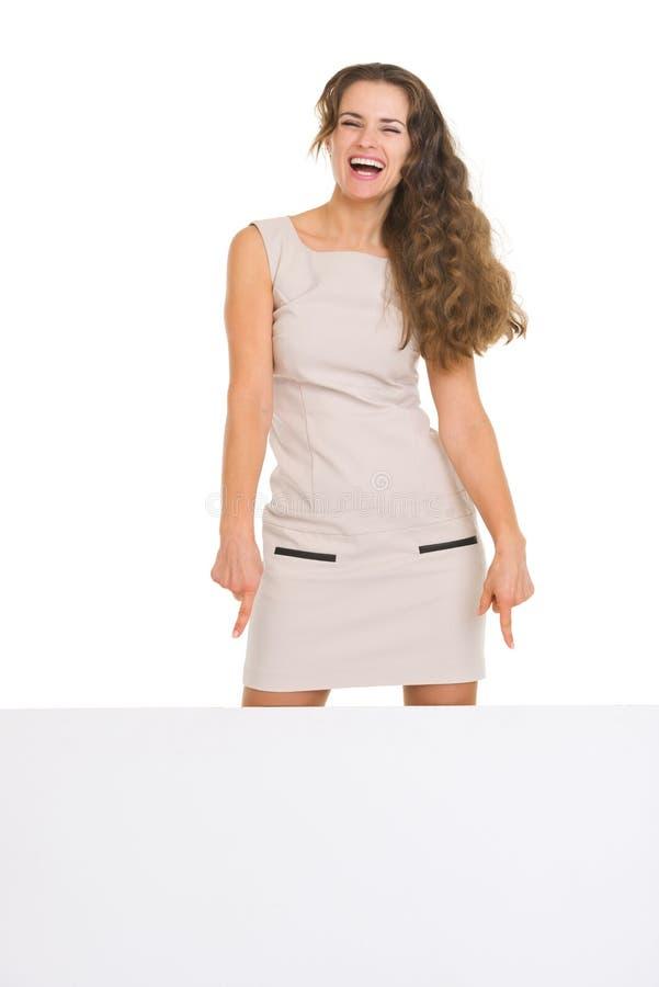 Jeune femme heureuse se dirigeant vers le bas sur le panneau-réclame vide image stock