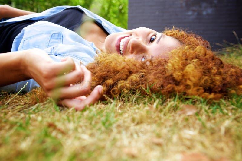 Jeune femme heureuse se situant dans l'herbe en stationnement photos stock