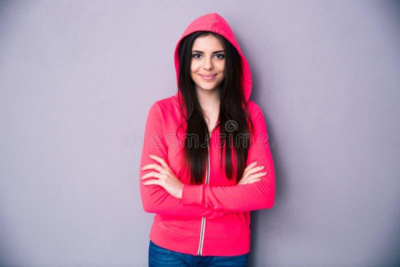 Jeune femme heureuse se tenant avec des bras pliés photographie stock