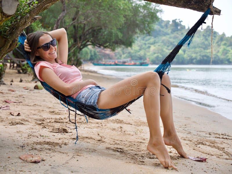 Jeune femme heureuse se trouvant sur l'hamac à la plage sablonneuse images libres de droits