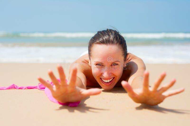 Jeune femme heureuse se trouvant sur le sable image stock