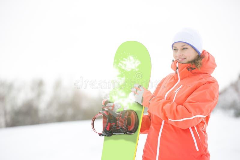 Jeune femme heureuse semblant partie tout en tenant le surf des neiges dans la neige image stock