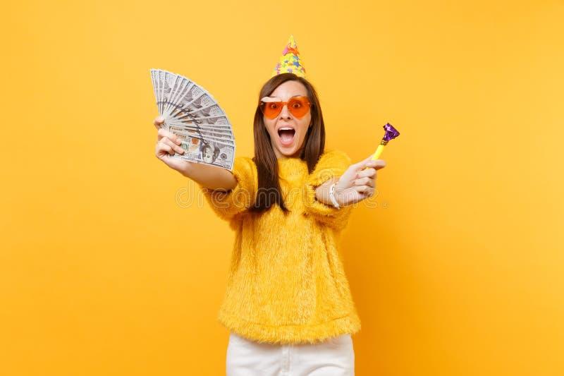 Jeune femme heureuse stupéfaite dans le chapeau orange d'anniversaire en verre de coeur avec jouer un bon nombre de paquet de par photographie stock