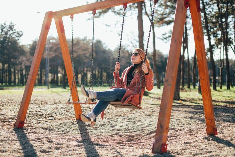 Jeune femme heureuse sur l'oscillation dans le terrain de jeu photo stock