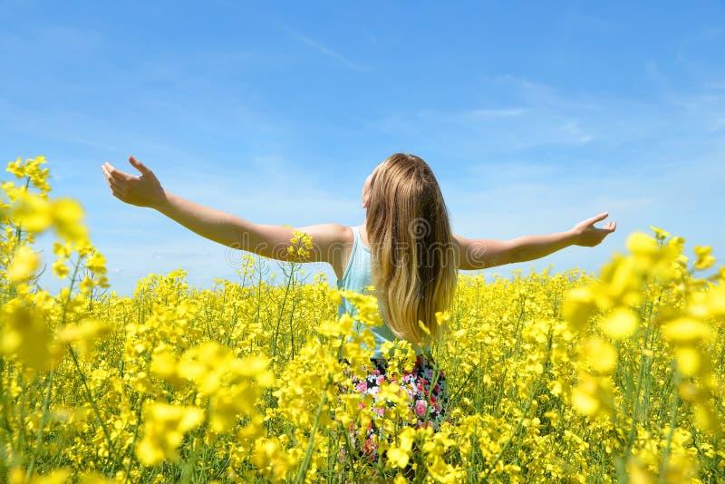Jeune femme heureuse sur le gisement de floraison de graine de colza photo libre de droits