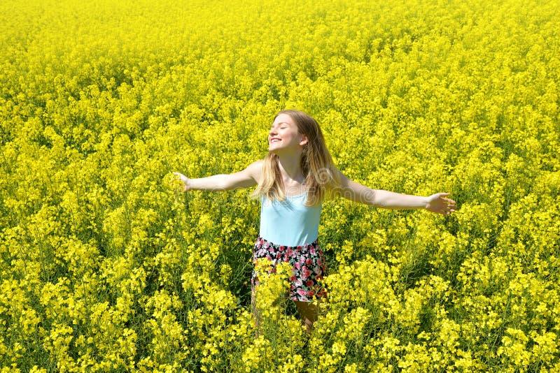 Jeune femme heureuse sur le gisement de floraison de graine de colza photo stock