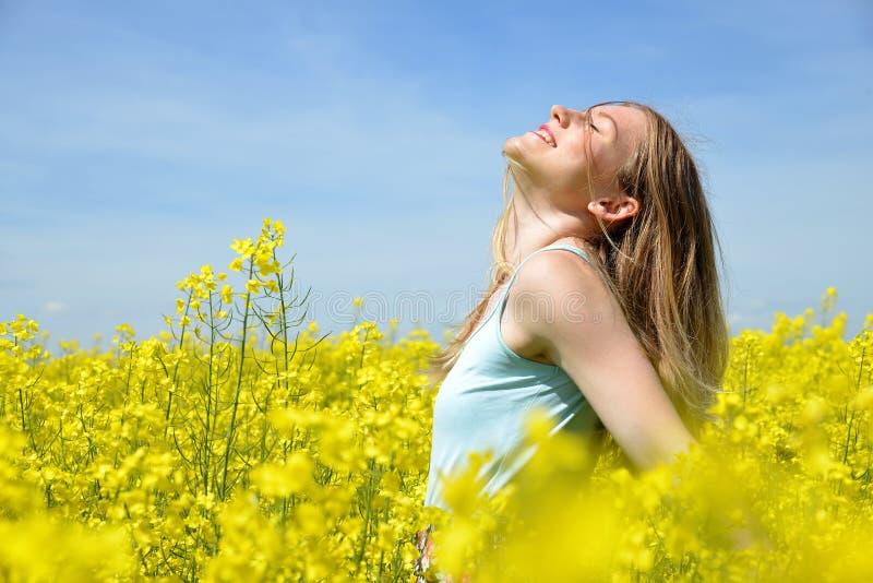 Jeune femme heureuse sur le gisement de floraison de graine de colza photographie stock