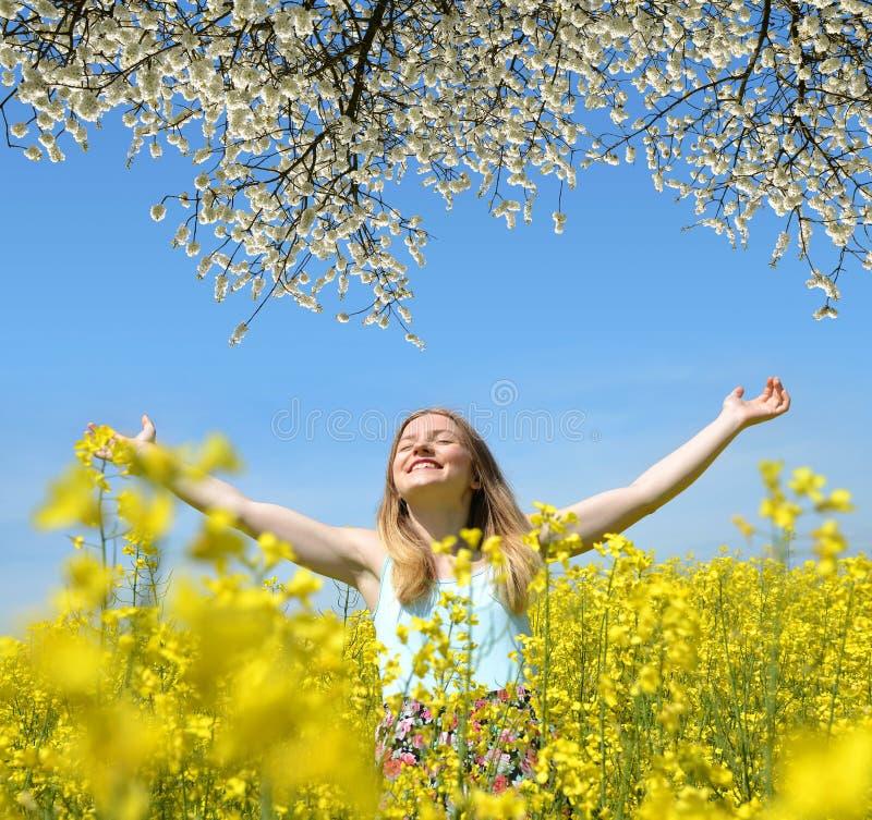 Jeune femme heureuse sur le gisement de floraison de graine de colza images libres de droits