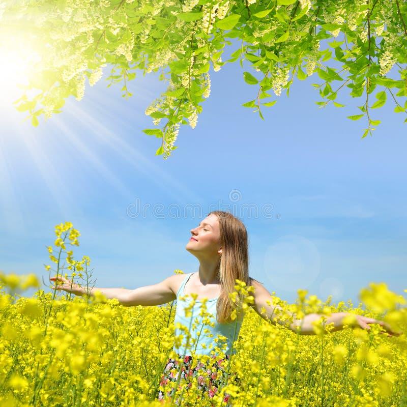 Jeune femme heureuse sur le gisement de floraison de graine de colza photographie stock libre de droits