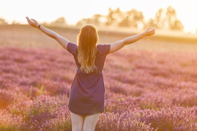 Jeune femme heureuse sur le gisement de lavande au coucher du soleil photo libre de droits