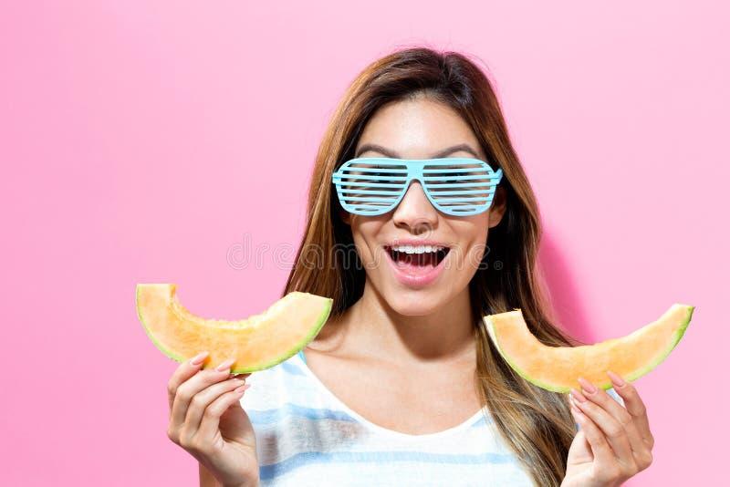 Jeune femme heureuse tenant des tranches de cantaloup photos stock