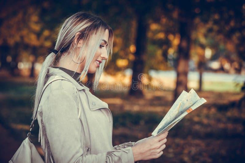 Jeune femme heureuse tenant la carte de la ville dans des ses mains photographie stock libre de droits