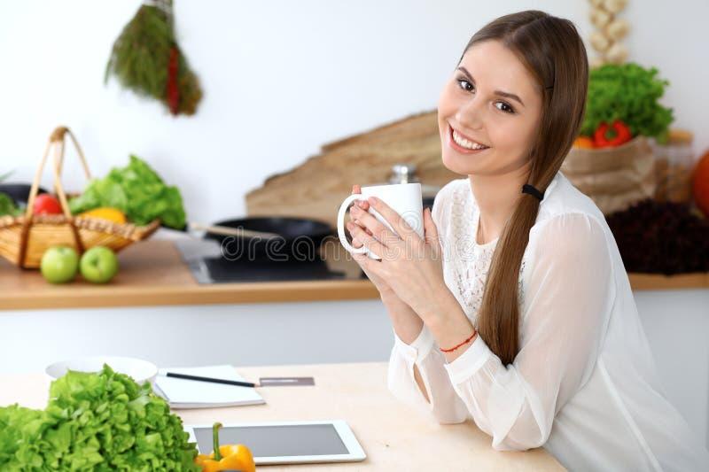 Jeune femme heureuse tenant la tasse blanche et regardant la caméra tout en se reposant à la table en bois dans la cuisine parmi  images stock