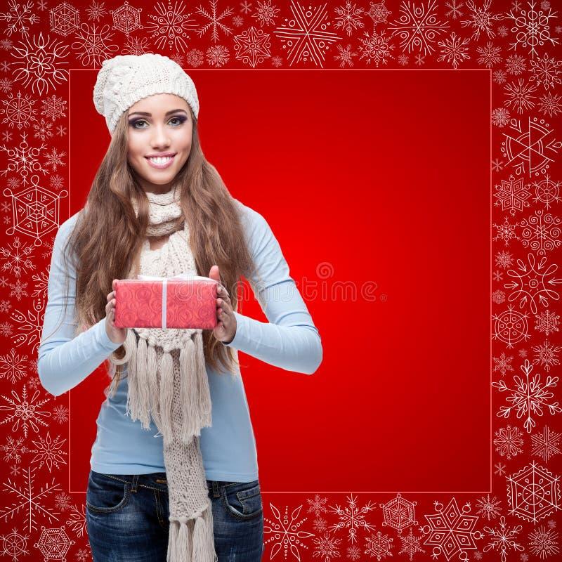 Jeune femme heureuse tenant le cadeau au-dessus du fond d'hiver image libre de droits