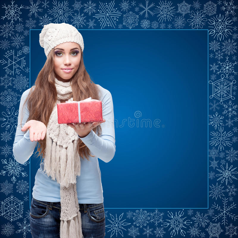 Jeune femme heureuse tenant le cadeau au-dessus du fond d'hiver photos libres de droits