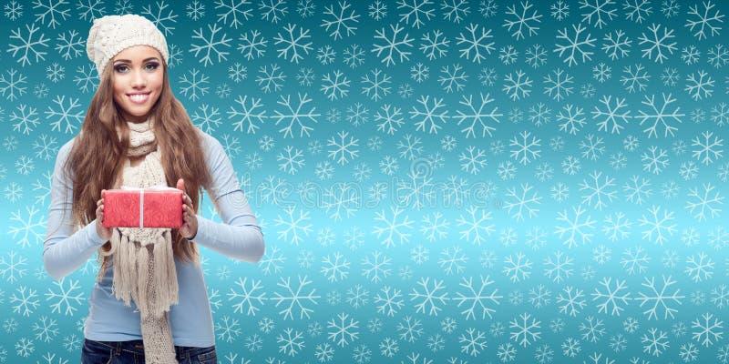 Jeune femme heureuse tenant le cadeau au-dessus du fond d'hiver images libres de droits