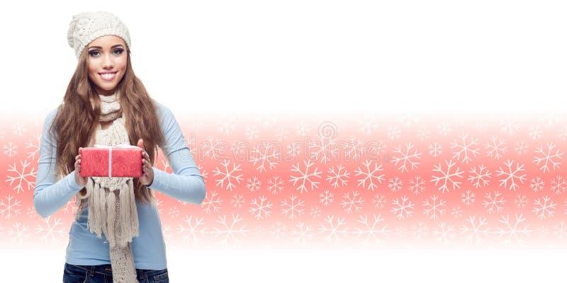 Jeune femme heureuse tenant le cadeau au-dessus du fond d'hiver photographie stock