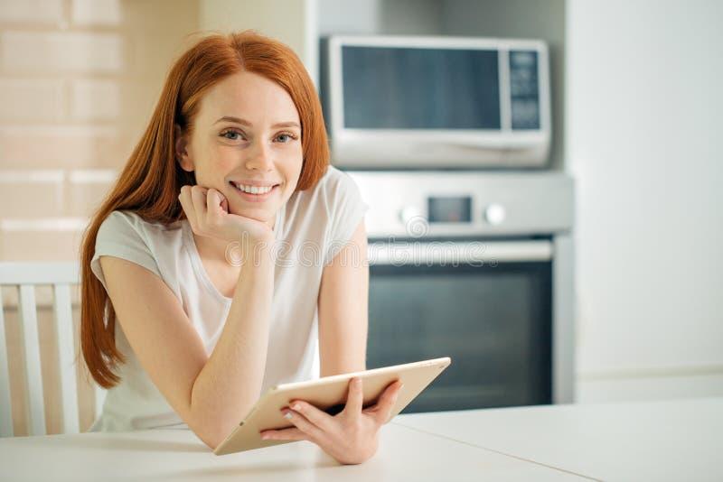 Jeune femme heureuse tenant le comprimé et regardant l'appareil-photo photo libre de droits