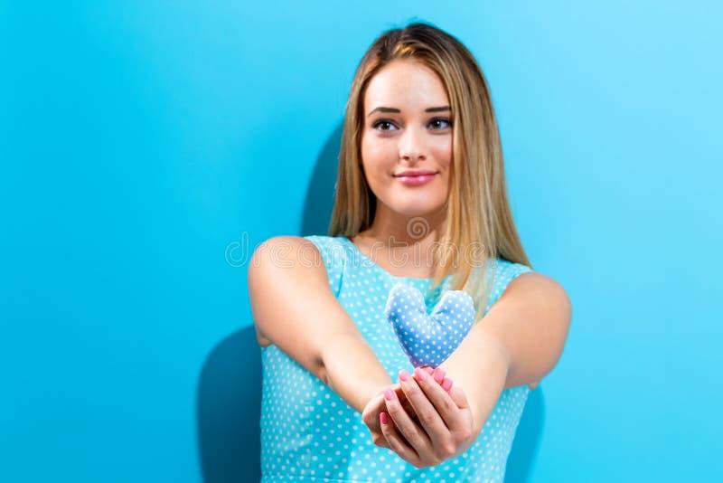 Jeune femme heureuse tenant le coussin de coeur photographie stock libre de droits
