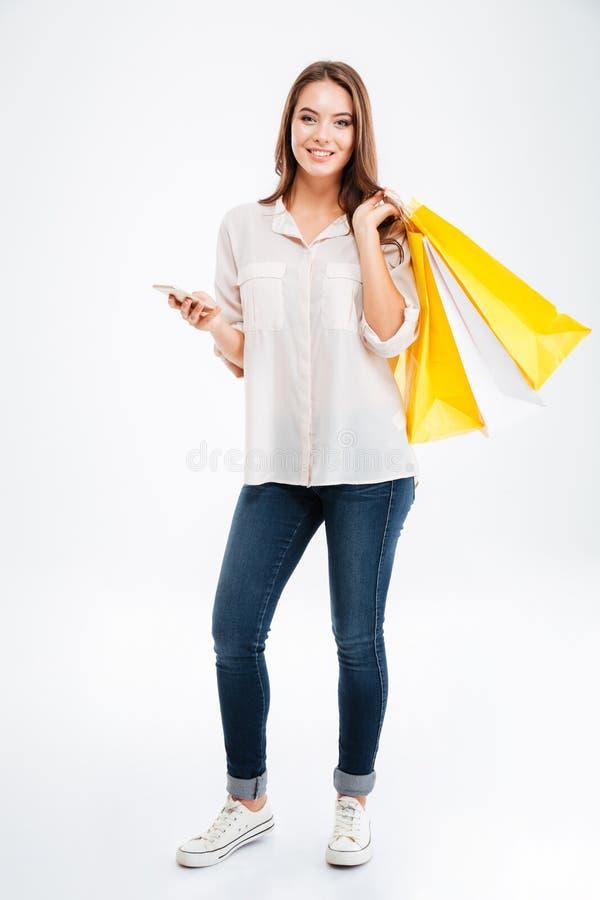 Jeune femme heureuse tenant les paniers et le téléphone portable images stock
