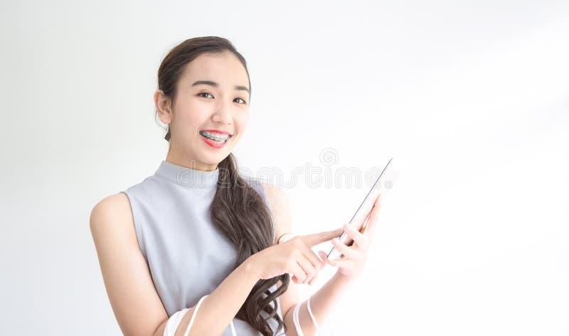 Jeune femme heureuse tenant les paniers et le téléphone portable Fait des achats en ligne sur un comprimé Achats femelles par les images libres de droits