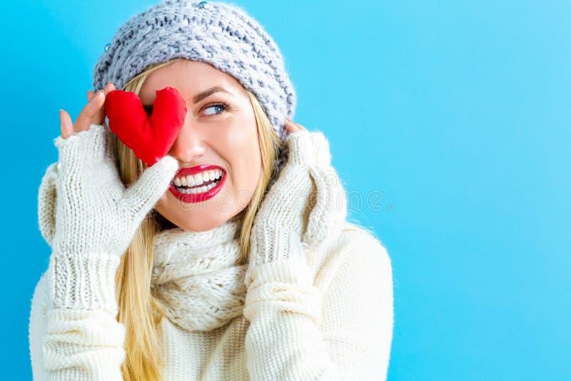 Jeune femme heureuse tenant un coussin de coeur photo libre de droits