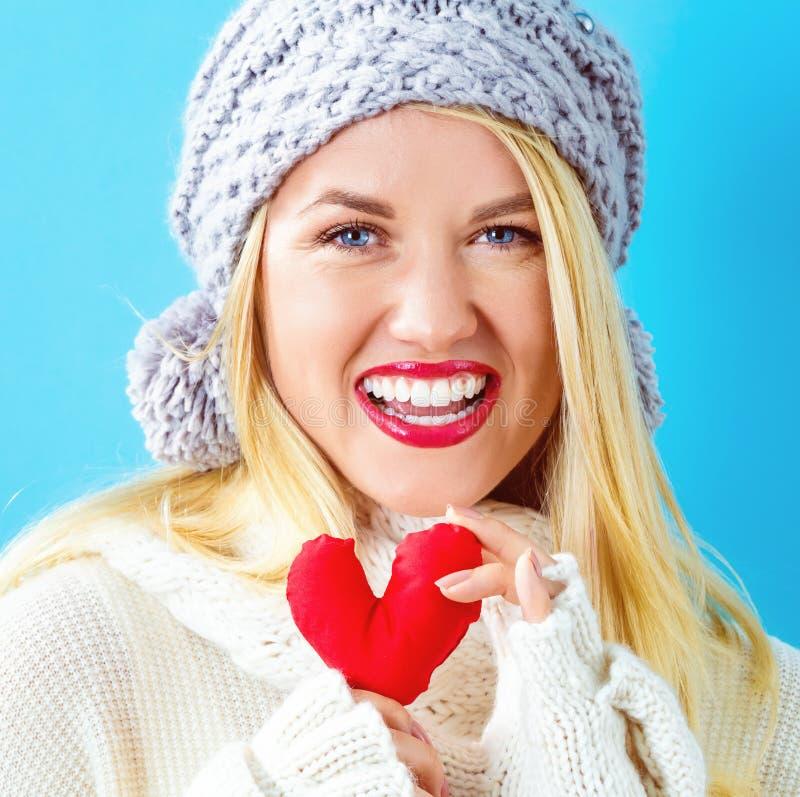 Jeune femme heureuse tenant un coussin de coeur photo stock