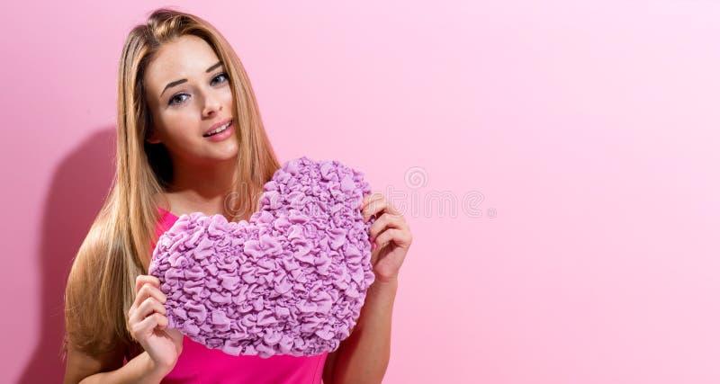 Jeune femme heureuse tenant un coussin de coeur photographie stock libre de droits