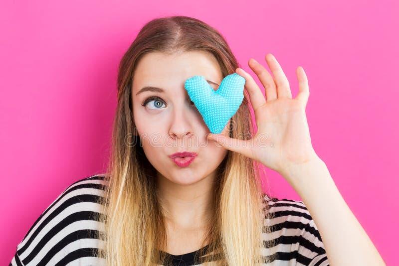 Jeune femme heureuse tenant un coussin de coeur photos stock