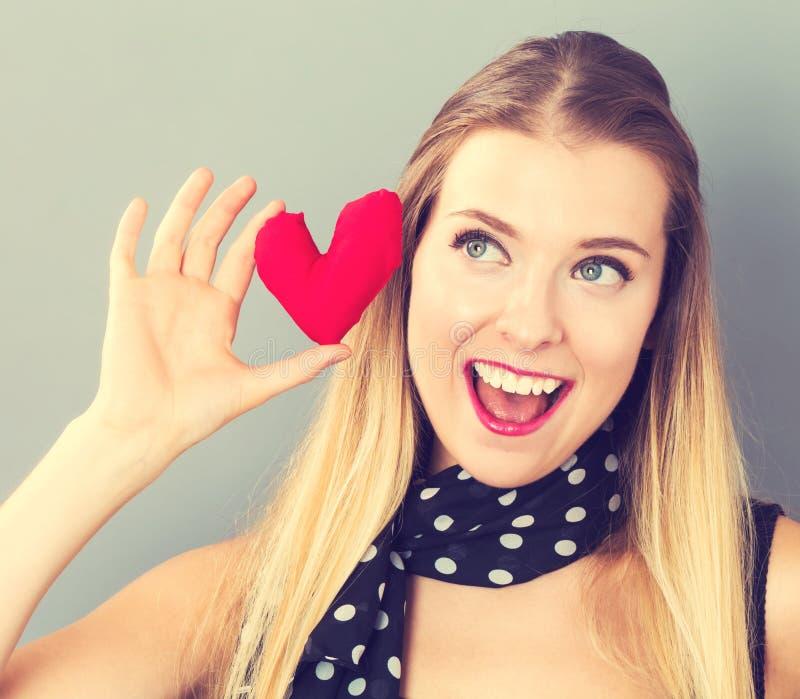 Jeune femme heureuse tenant un coussin de coeur photographie stock