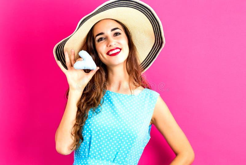 Jeune femme heureuse tenant un coussin de coeur images libres de droits