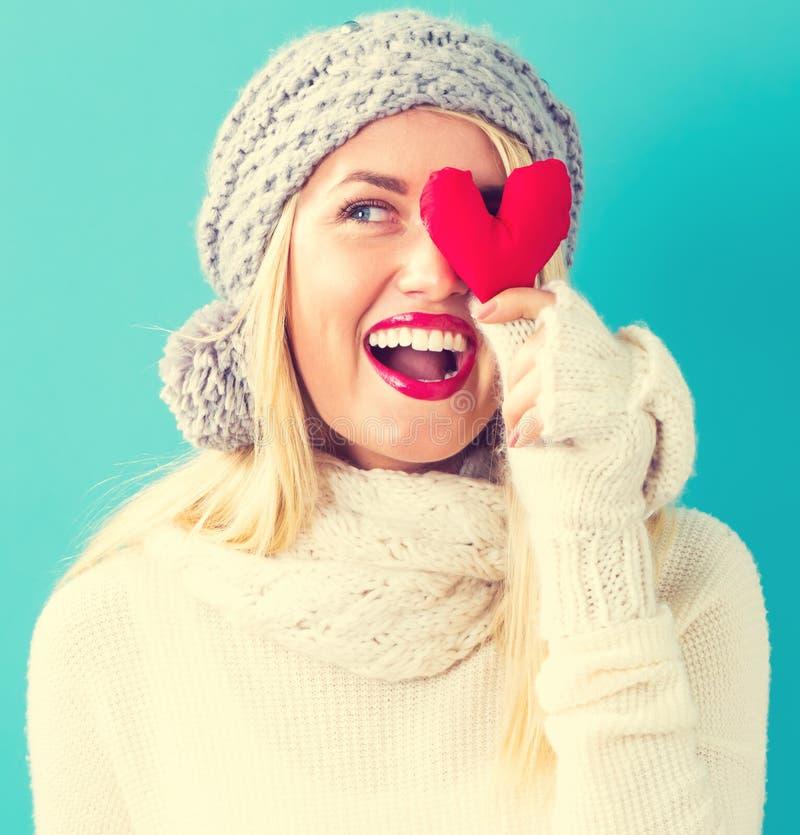 Jeune femme heureuse tenant un coussin de coeur image libre de droits