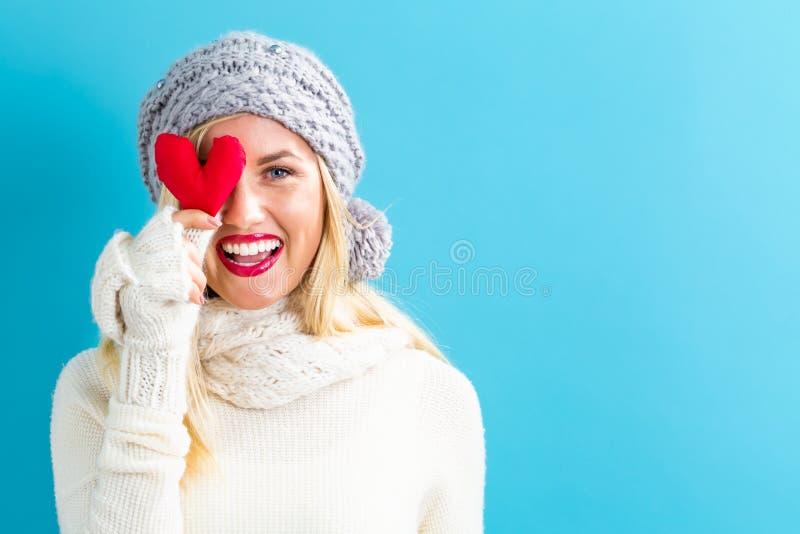 Jeune femme heureuse tenant un coussin de coeur images stock