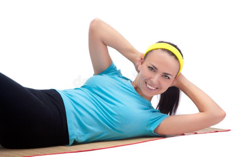 Jeune femme heureux faisant l'exercice de forme physique sur le couvre-tapis images stock