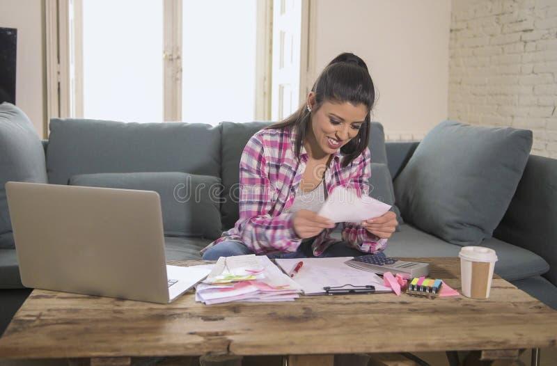 Jeune femme hispanique attirante et heureuse vérifiant des dépenses de papiers de banque de factures et des paiements mensuels so images stock